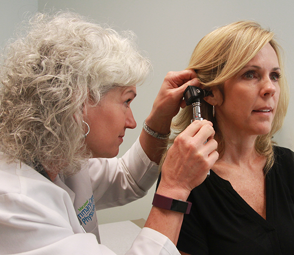 A doctor examining a patients' ear.